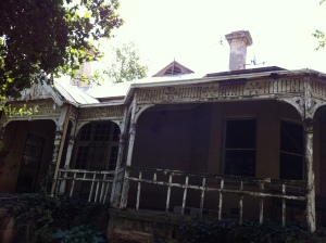 Intricate woodwork details on the verandah of this rundown house